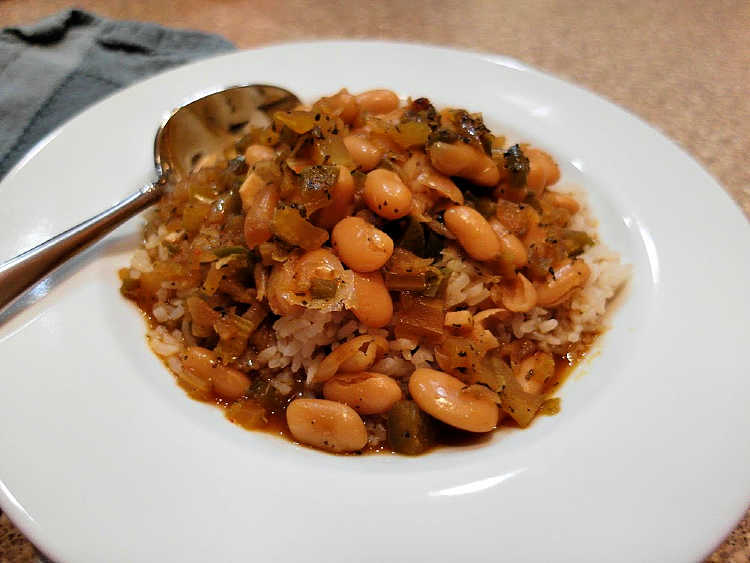 a dish of Creole White beans over rice with a spoon in it