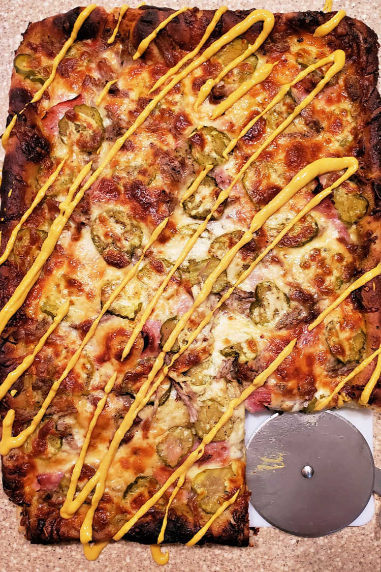 overhead shot of a cubano pizza or cuban sandwich pizza with zigzags of yellow mustard on it and one slice cut out