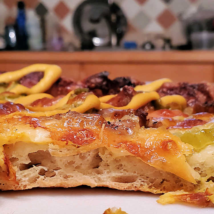 close up of a cut slice of cuban pizza showing the open airy crust structure of the grandma pizza dough.