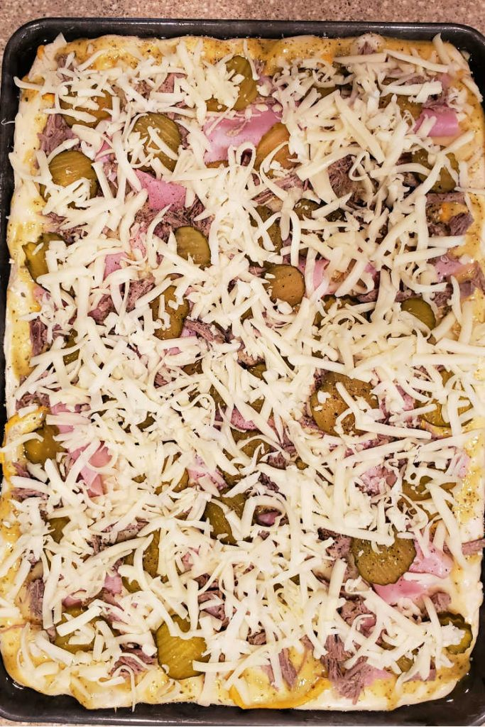 overhead shot of a fully loaded cubano pizza before baking