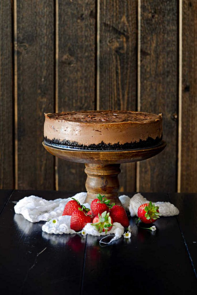a whole Nutella cheesecake on a wooden pedestal with strawberries around the base