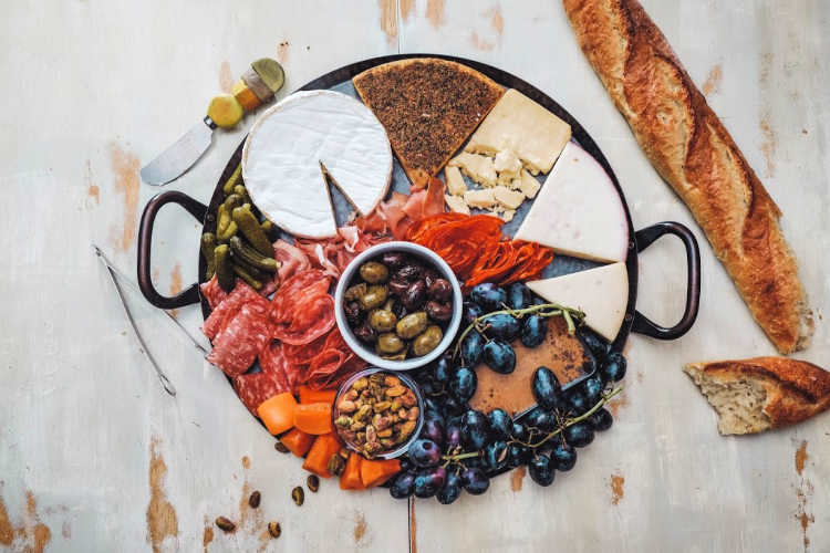 overhead shot of round tray with cheese, pickles, olives, fruit, cured meat, and bread