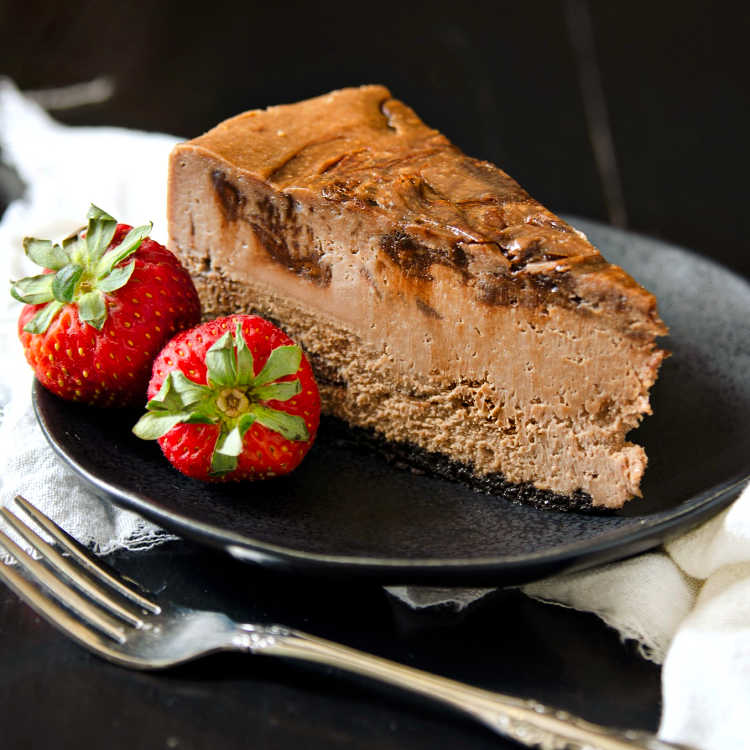 square image of slice of nutella cheesecake on a plate with 2 strawberries