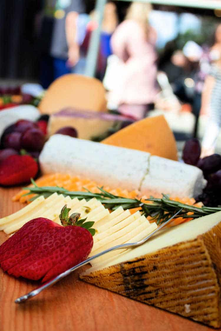 a log of goat cheese, a wedge of hard cheese and slices of cheese with a sliced strawberry and herbs on a board