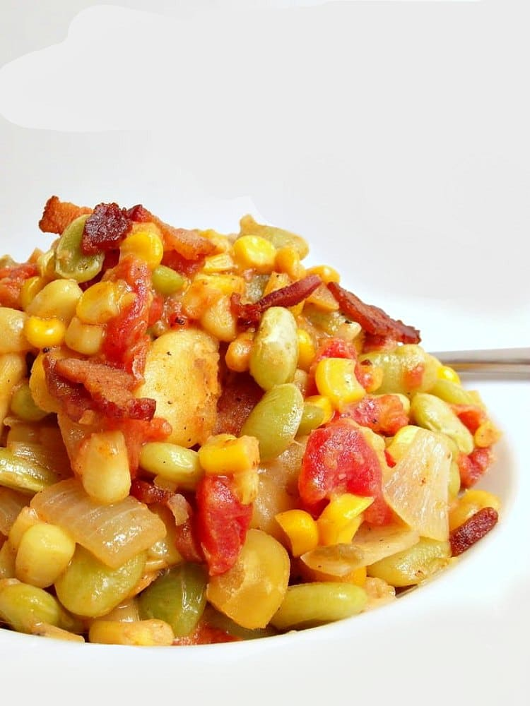 vertical image of a mound of spicy succotash with corn, lima beans, fava beans and bacon on a white plate