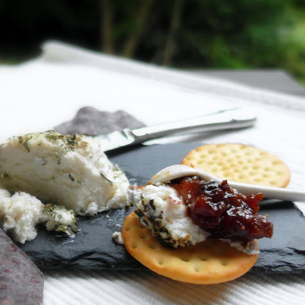 fig jam and goat cheese on a cracker with goat cheese and a knife on a slate board