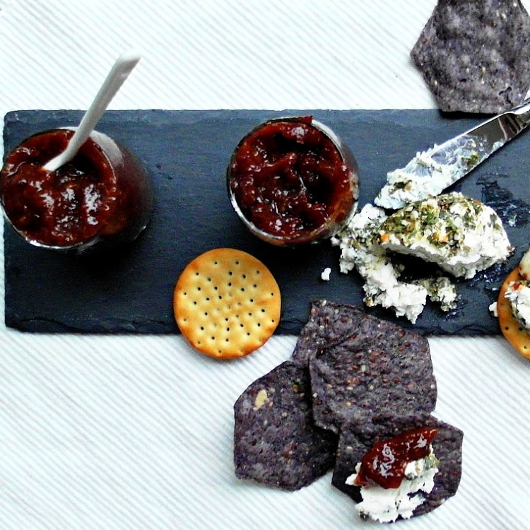 overhead shot of blue tortilla chips, herbed goat cheese, crackers, and savory fig jam