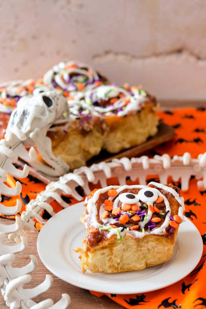 a cinnamon roll decorated for Halloween on a plate with a plastic snake skelteon
