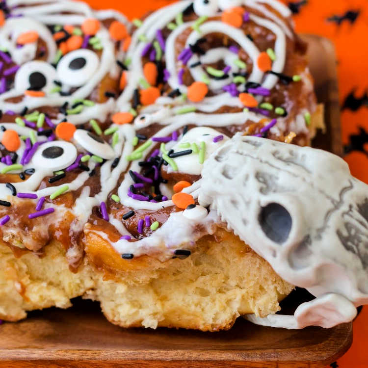 snake skull taking a bite out of halloween decorated cinnamon rolls on a plate