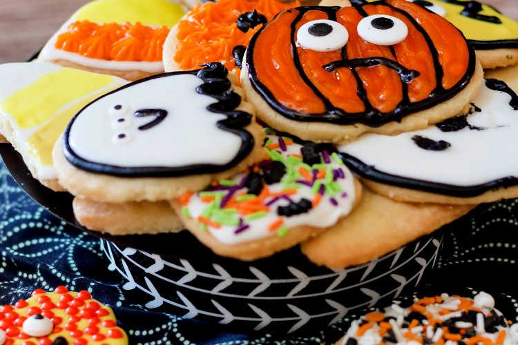 lots of decorated Halloween shortbread cookies on a spider web-printed cloth background