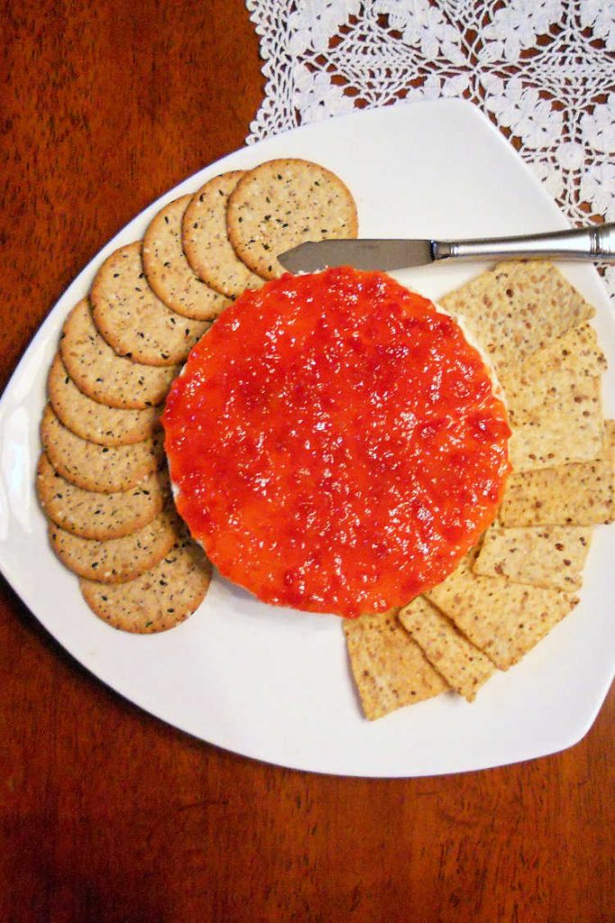 overhead shot of savory cheesecake topped with pepper jelly with crackers on a white plate