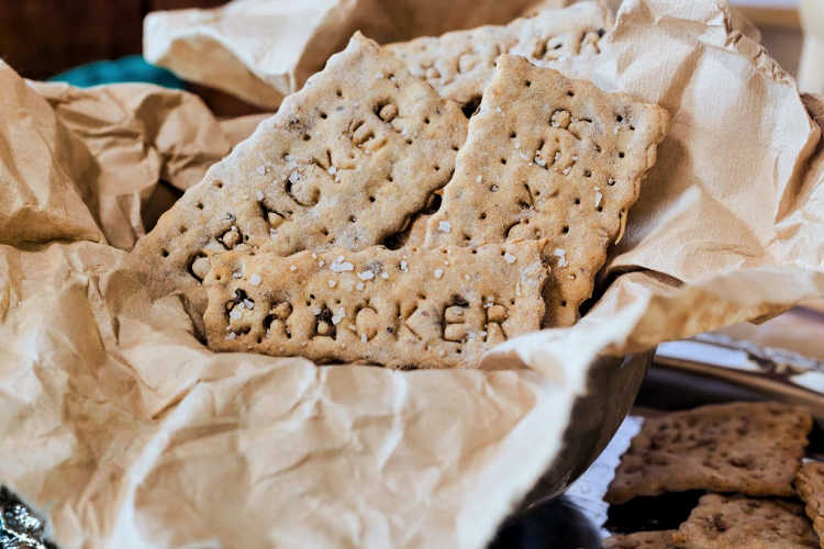 """Close up of crackers with the word """"cracker"""" pressed into them."""