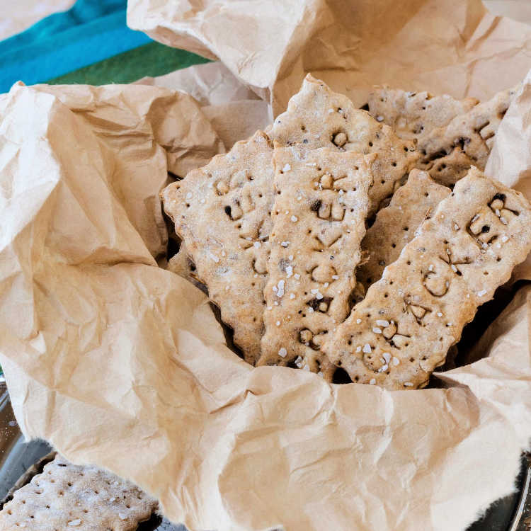 """Homemade crackers that say """"cracker"""" on them, served in a bowl."""