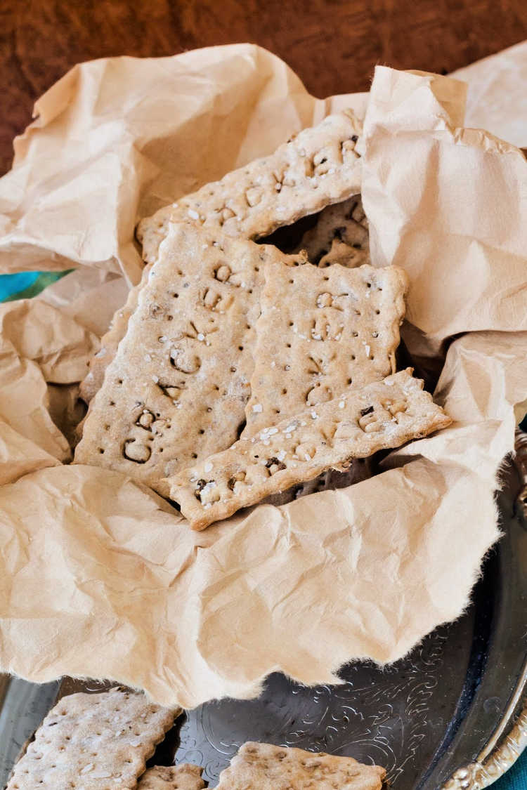 """Spent grain crackers with the word """"cracker"""" embossed on each one in a basket lined with tan paper."""