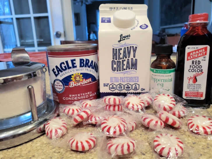 ingredients for homemade peppermint ice creams: salt, sweetened condensed milk, heavy cream, peppermint oil, red food coloring, and crushed mints