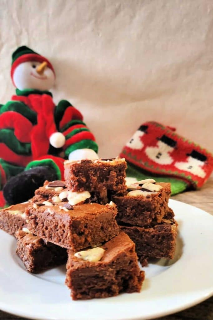 a white plate of ghirardelli peppermint bark brownies with a Christmas stocking and decorative snowman in the background