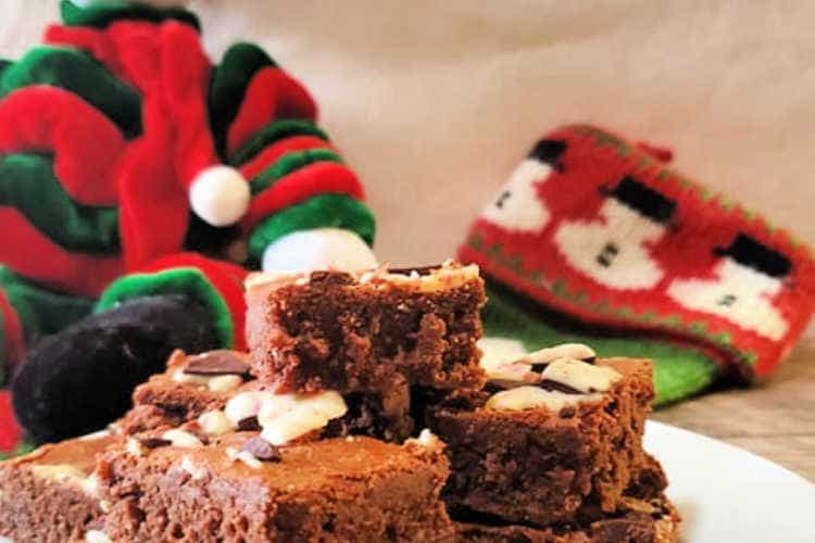 white plate of peppermint bark brownies with a Christmas stocking and decorative snowman in the background