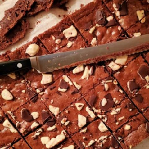 overhead shot of a slab of sliced brownies with a serrated knife