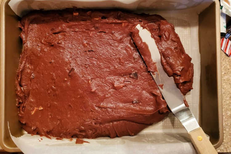overhead shot of a rectangular pan with brownie batter being spread in it with an offset spatula