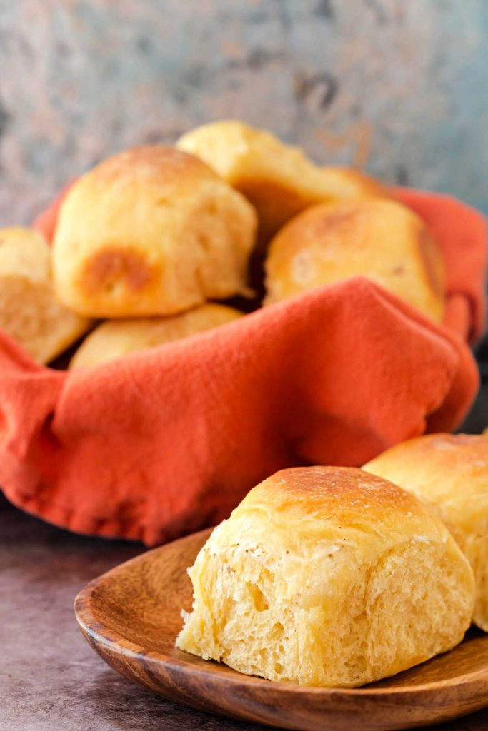 basket of rolls with an orange napkin and a cheese roll on a wooden plate