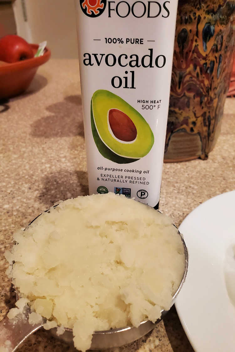a cup of mashed potato and a bottle of avocado oil