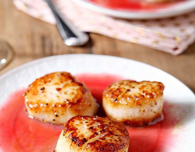 3 seared scallops on a white plate with a gastrique sauce