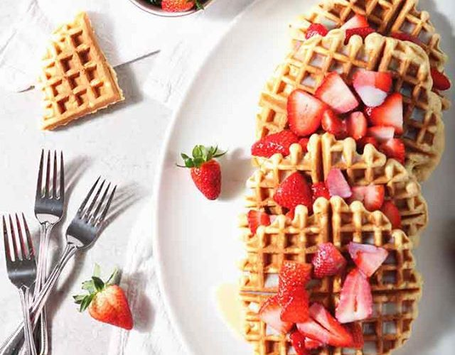 overhead shot of a plate of waffles with sliced strawberries