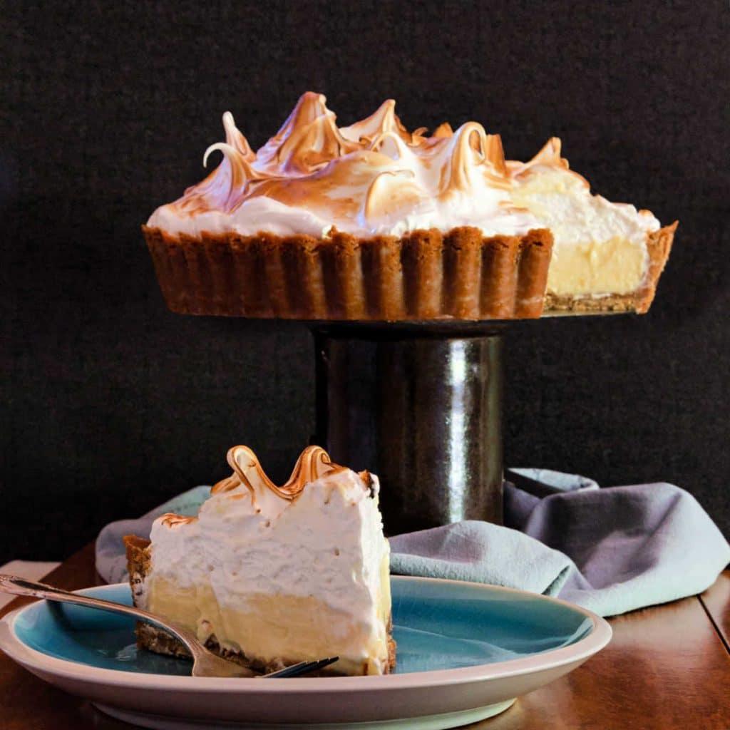 square image of lemon meringue tart on a pedestal and a slice on a plate