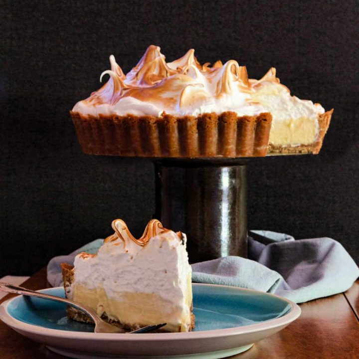 square image of lemon meringue pie on a pedestal and a slice on a plate
