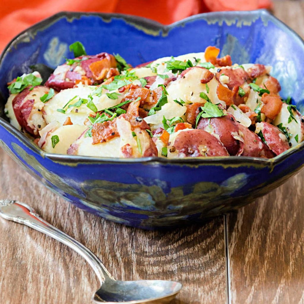 blue bowl of red-skinned potatoes with bacon and parsley
