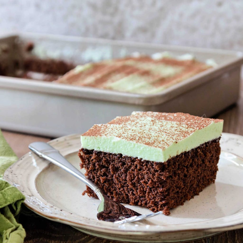 a piece of chocolate sheetcake with mint buttercream on a plate