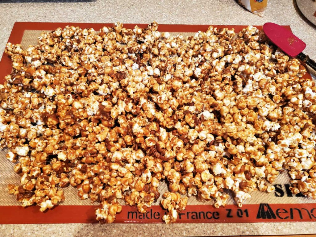 pumpkin spice popcorn spread out to cool on a Silpat