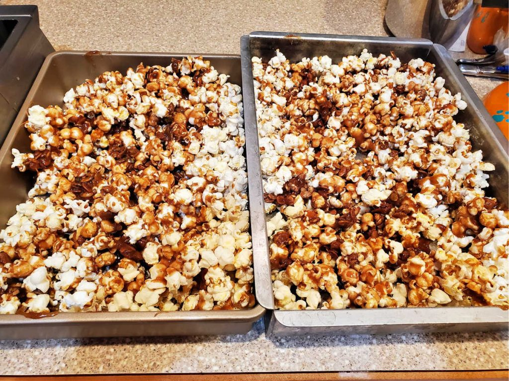 two pans with popcorn, candied pepitas, and caramel