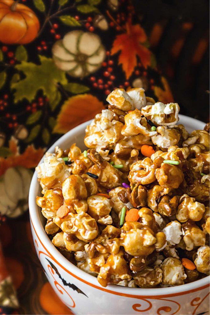 vertical image of bowl of pumpkin spice caramel corn