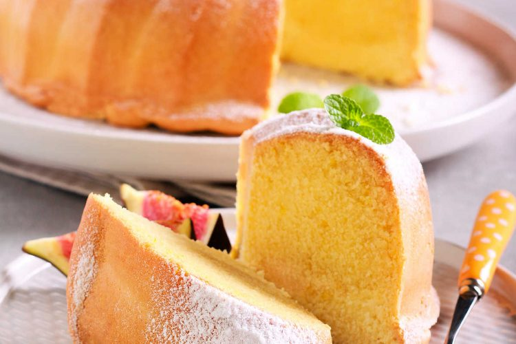 2 slices of lemon pound cake on a plate with the rest of the cake in the background